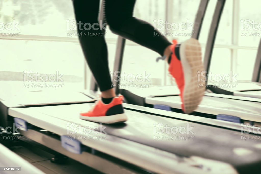 Blurry of  running sport shoes at the gym while a young caucasian woman is having jogging on the treadmill stock photo