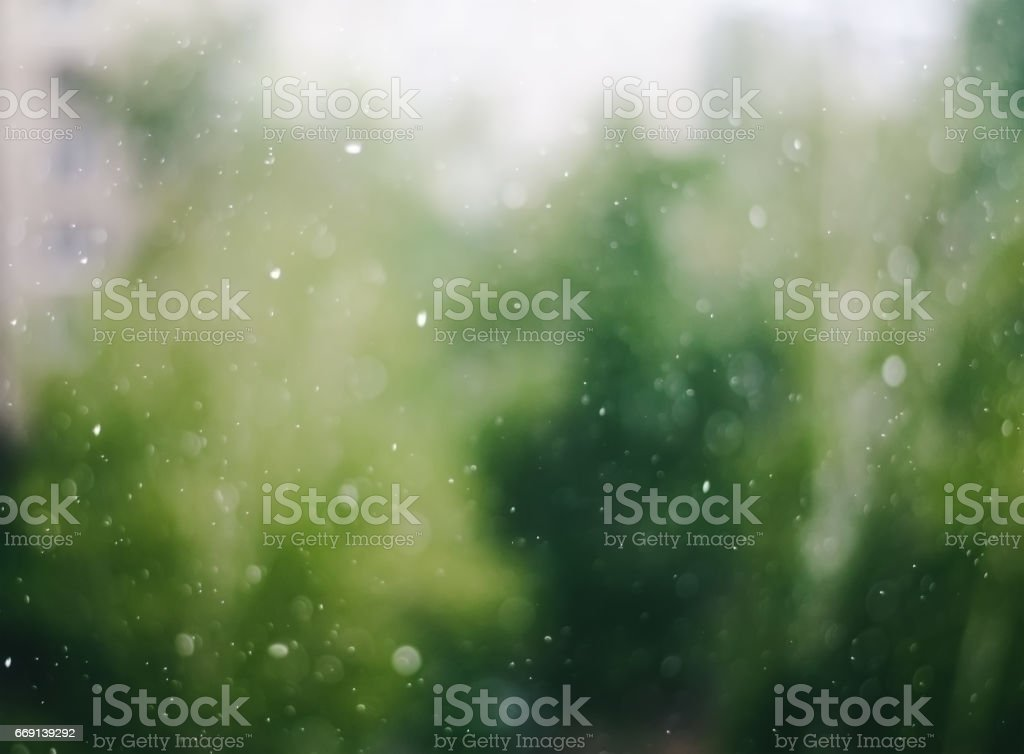 Blurry raindrops on window glass abstract background stock photo