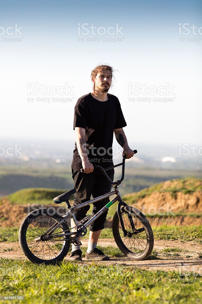 Bmx cyclist standing on a dirt road with his bicycle. stock photo