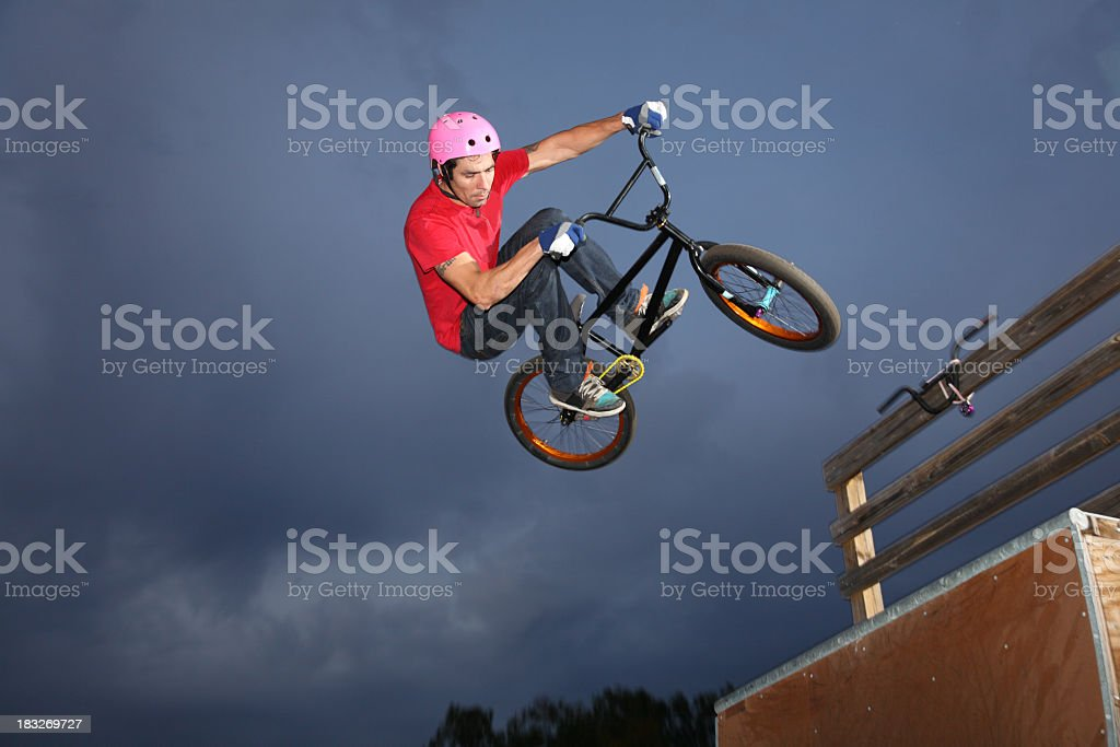BMXer Airborne In Dark Cloudy Sky royalty-free stock photo