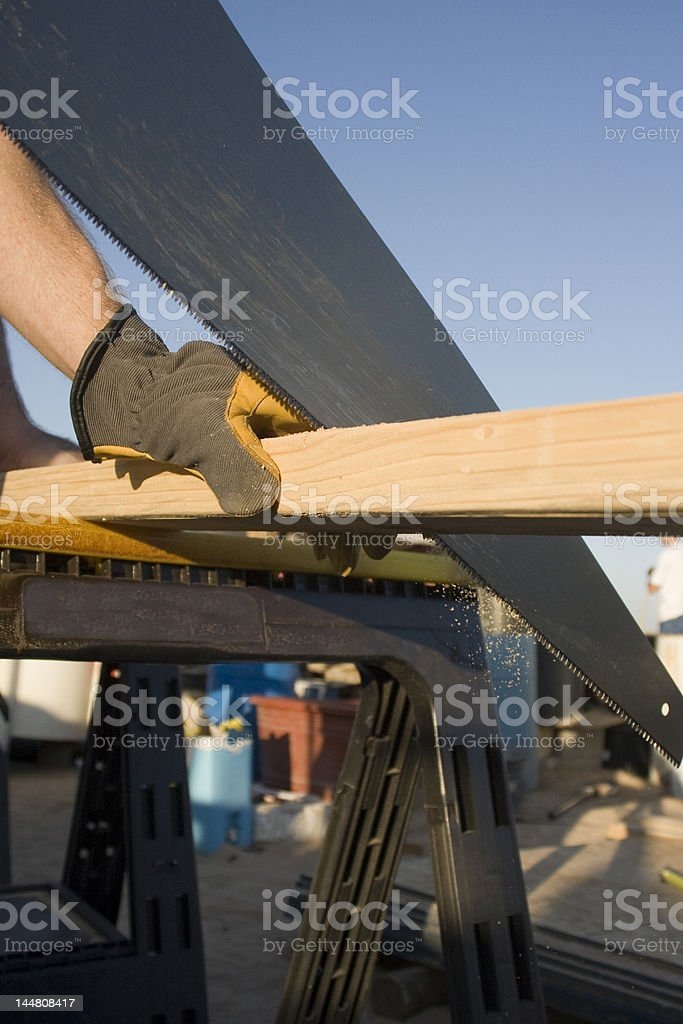 Board being cut with a hand saw royalty-free stock photo