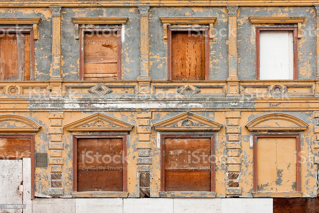 Boarded up derelict building facade peeling paint royalty-free stock photo