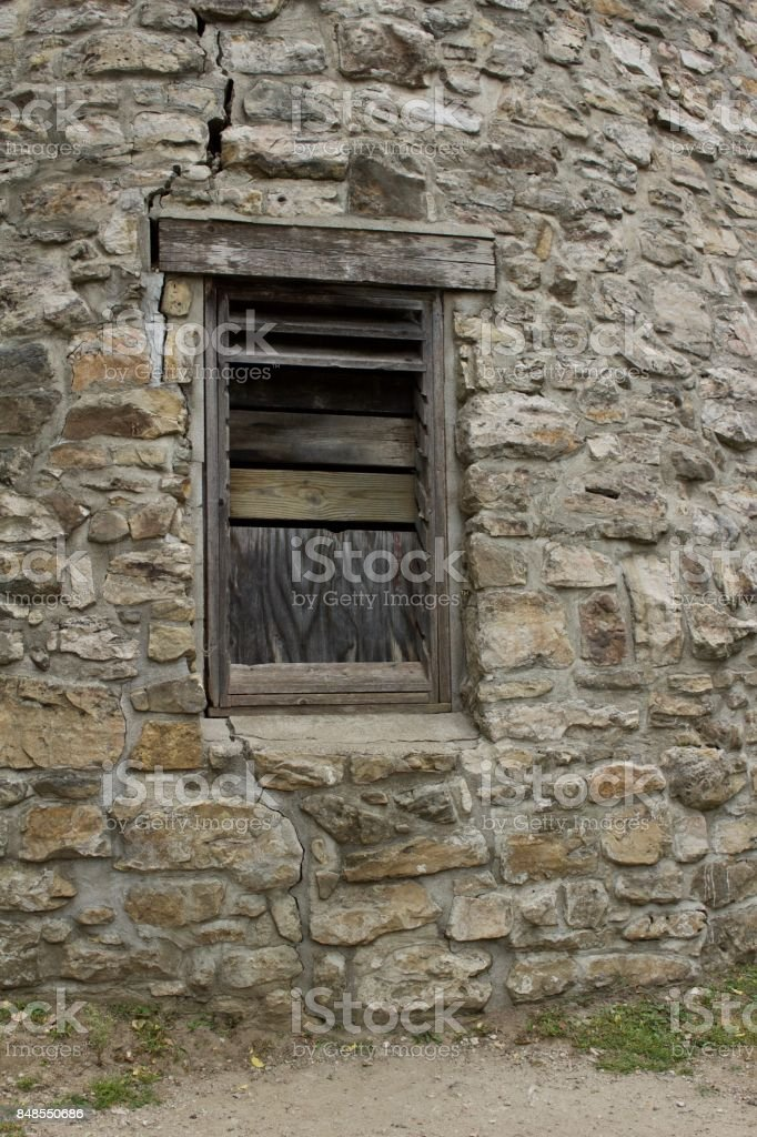 Boarded up wooden window entrance to old stone gristmill building stock photo