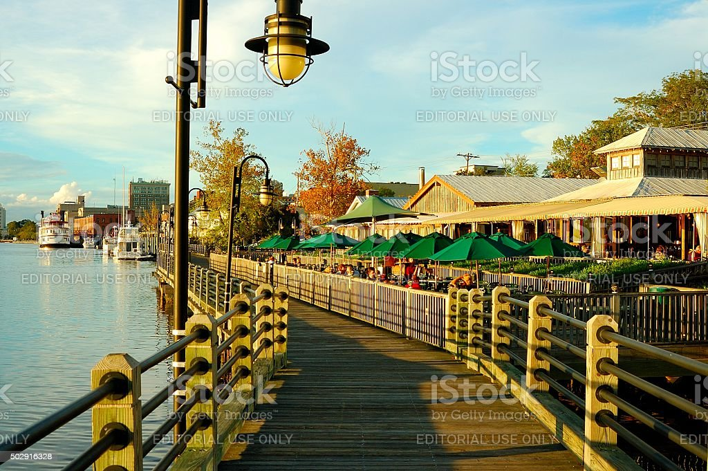 Boardwalk along the shore with restaurants and boats stock photo