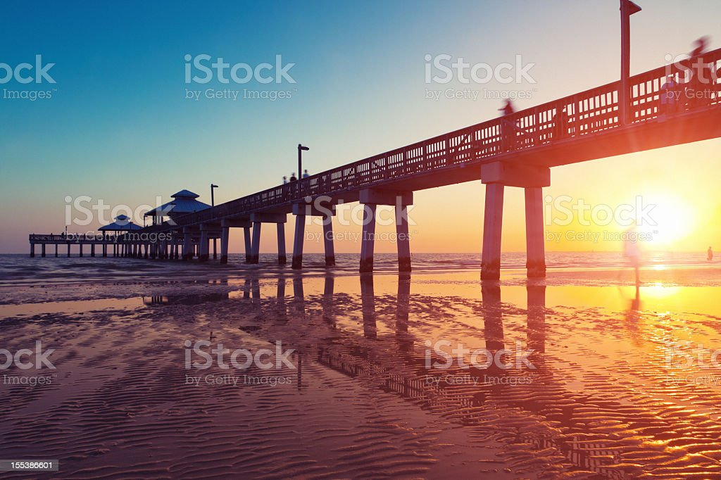 Boardwalk at sunset while the sun reflects off the water stock photo
