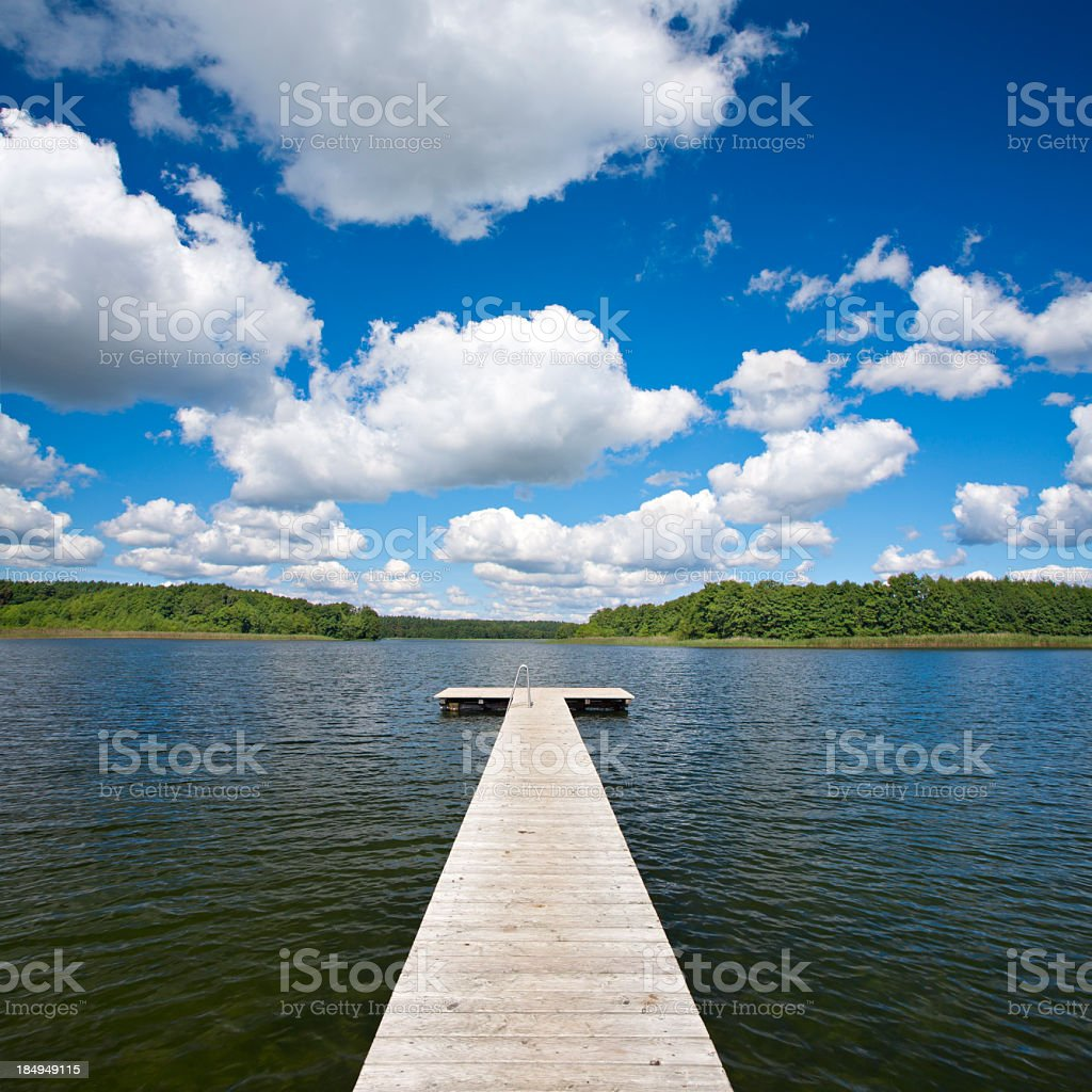 Boardwalk Dock on Lake under Cloudy Summer Sky royalty-free stock photo