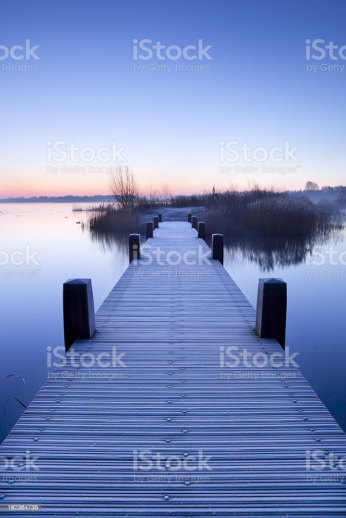 Boardwalk on a lake at dawn in winter, The Netherlands royalty-free stock photo