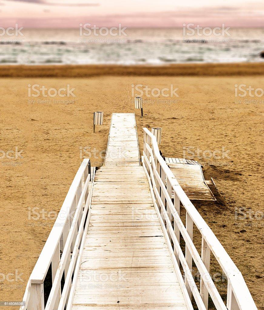 Boardwalk on the beach at sunset stock photo