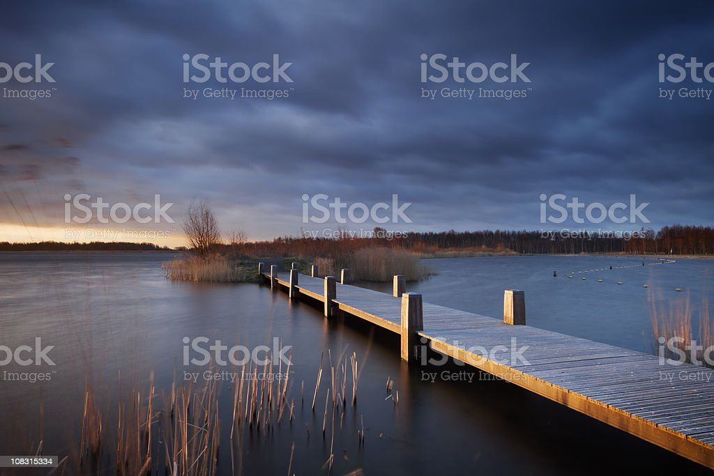 Boardwalk over a lake under stormy skies in The Netherlands royalty-free stock photo