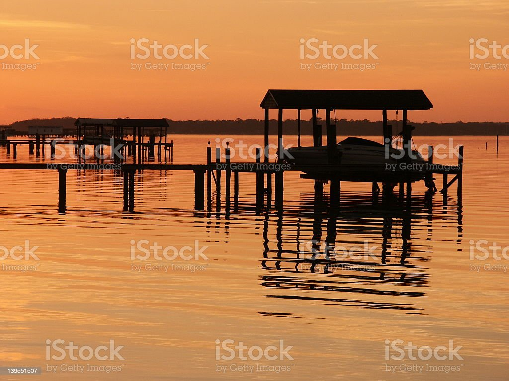 boat and dock at sunset stock photo