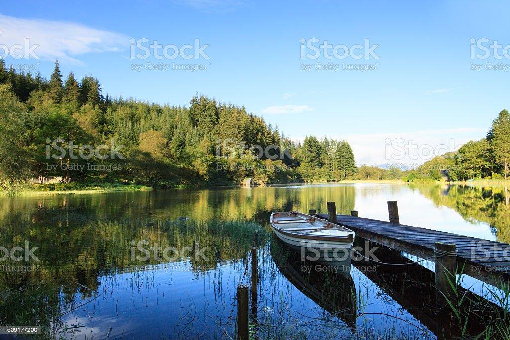 Boat and jetty, Loch Ard, Scotland. stock photo