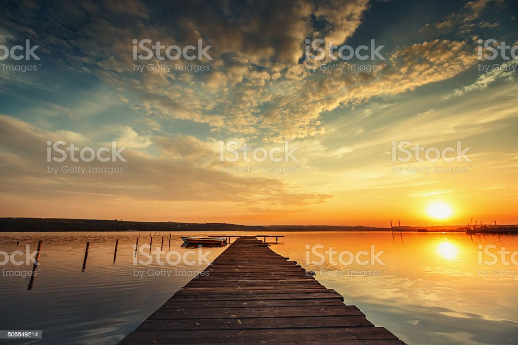 Boat and jetty on lake with water reflection stock photo