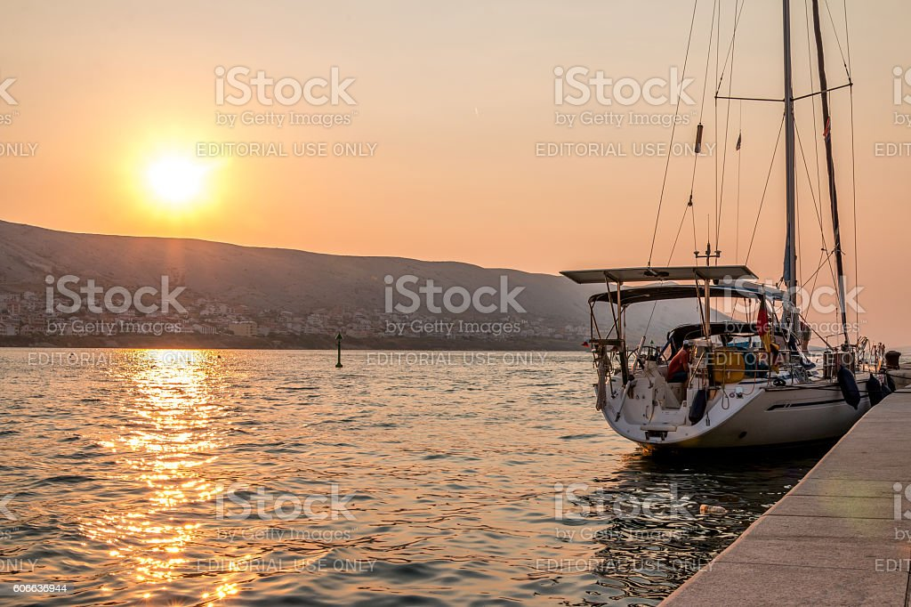 Boat at a small port in sunset. stock photo