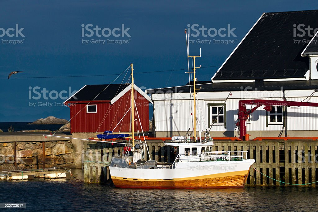 Boat at dock in the harbor of Henningsfaer, Norway stock photo
