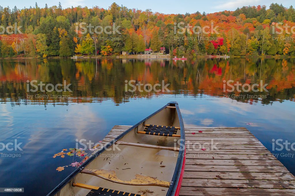 Boat at dock with fall foliage reflection on quiet lake stock photo