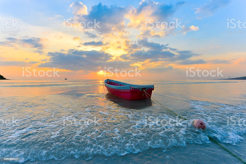 Boat at sunset beach stock photo
