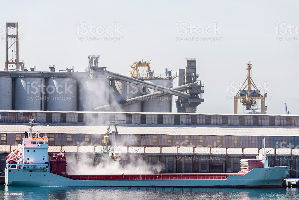 Boat being loaded of grain in the port stock photo