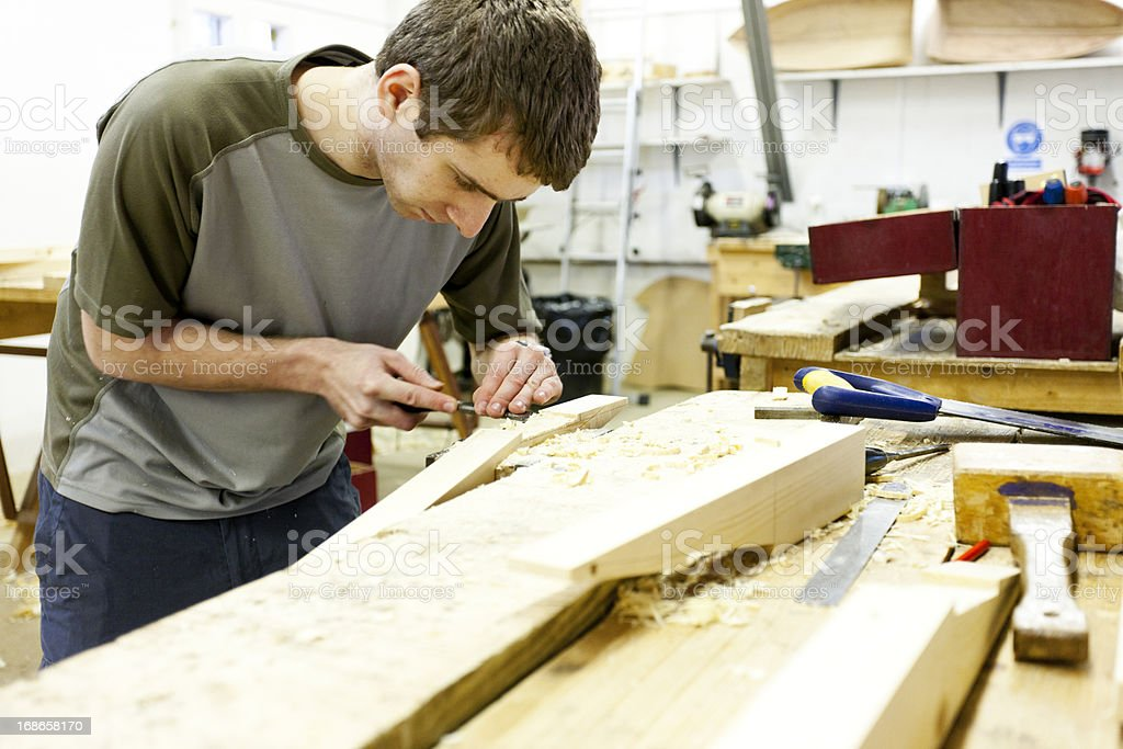 Boat builder working with a chisel royalty-free stock photo