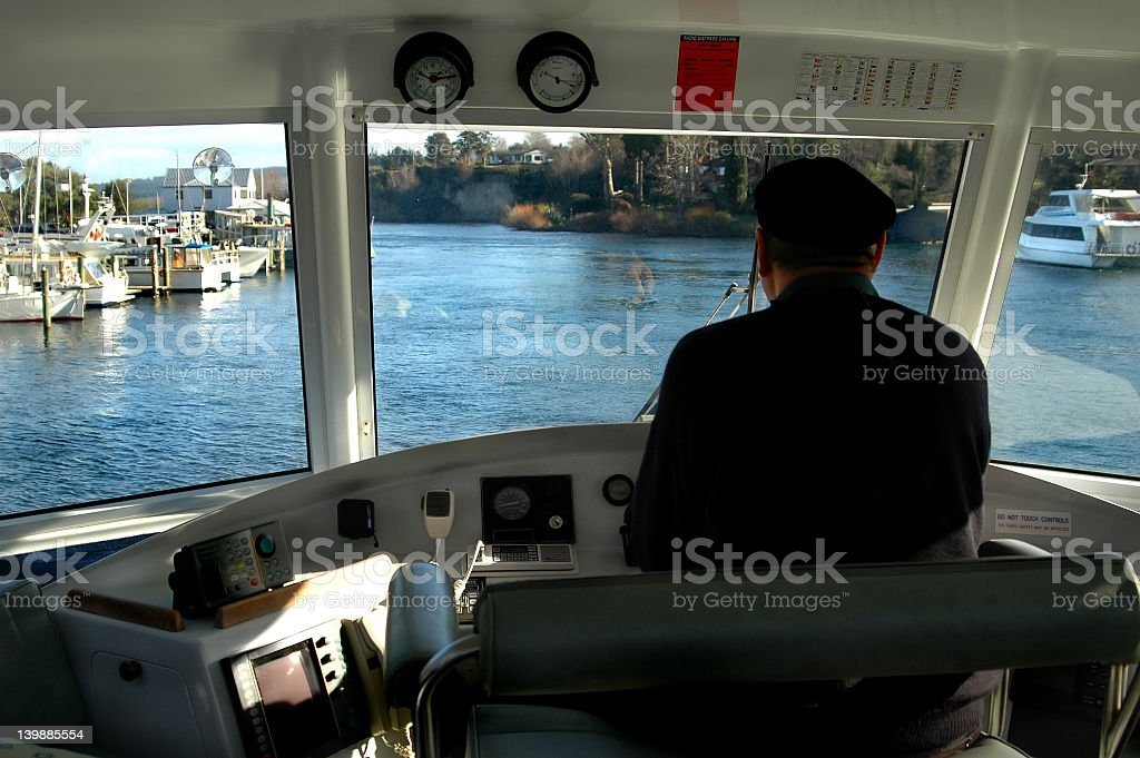 Boat captain looking out the front windows of his boat stock photo