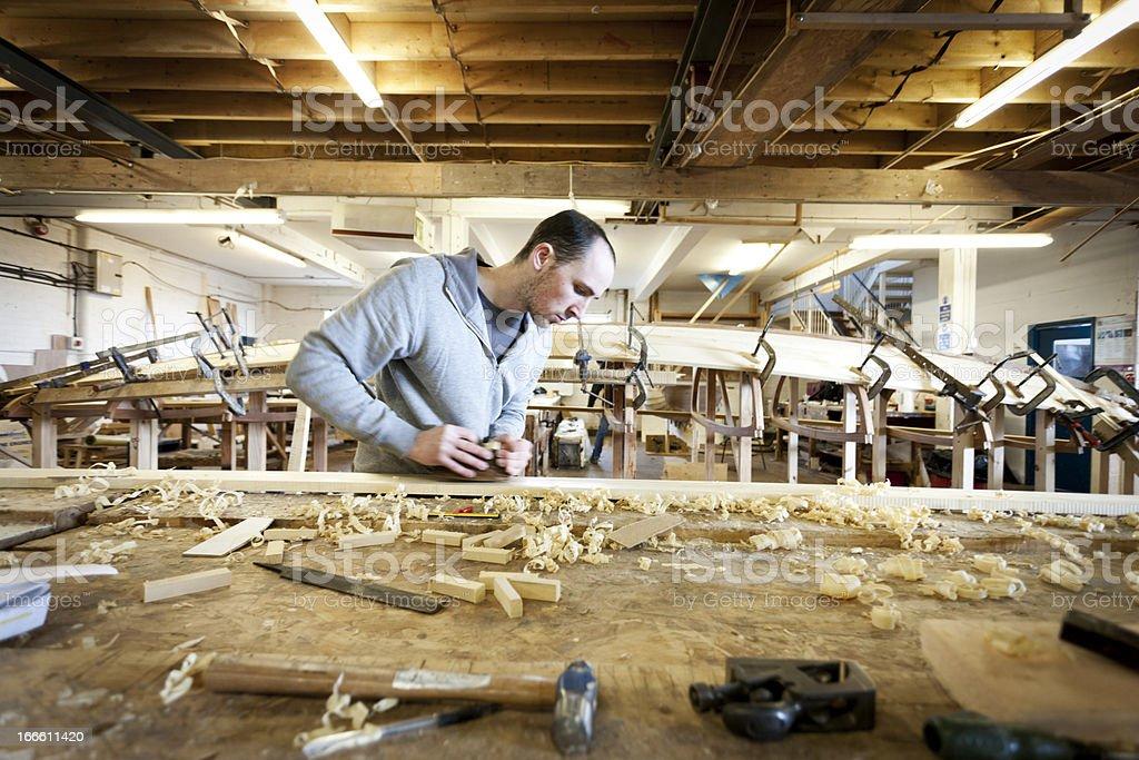 Boat carpenter, using a wood plane stock photo