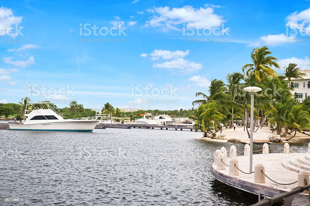 Boat cruising by waterfront of  Camana Bay on Grand Cayman stock photo