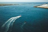 Boat cruising in ocean bay (tilt-shift lens view)