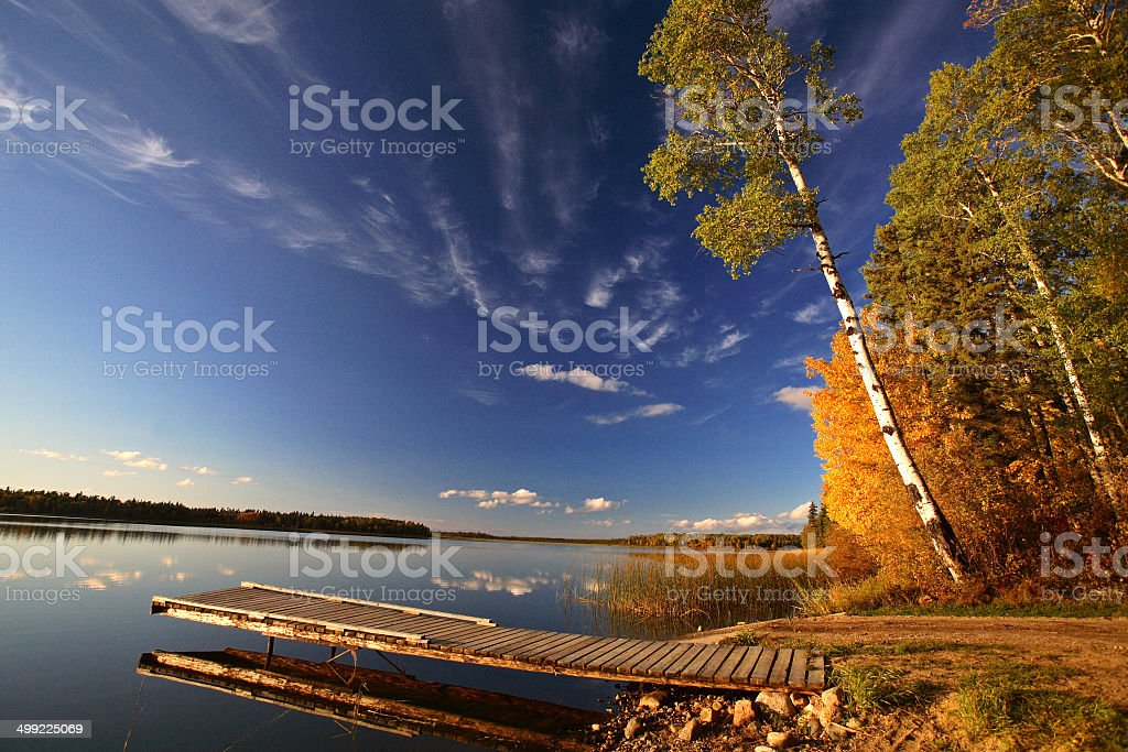 Boat dock and autumn trees along a Saskatchewan Lake stock photo