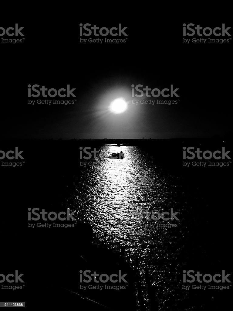 Boat drifting on black water in Noir style stock photo