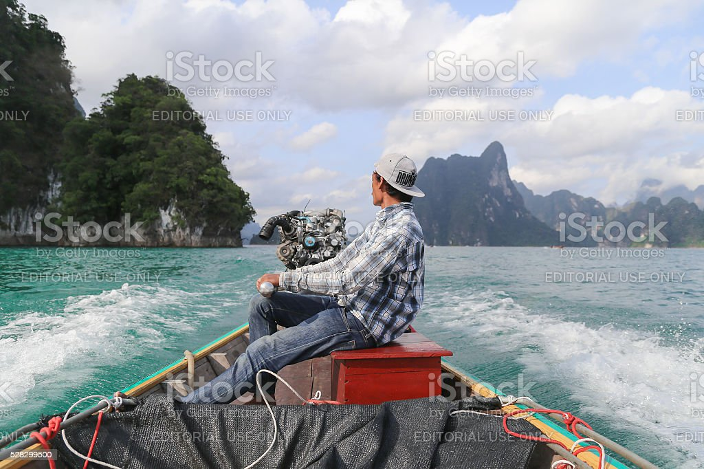 Boat driver in dam of Thailand stock photo