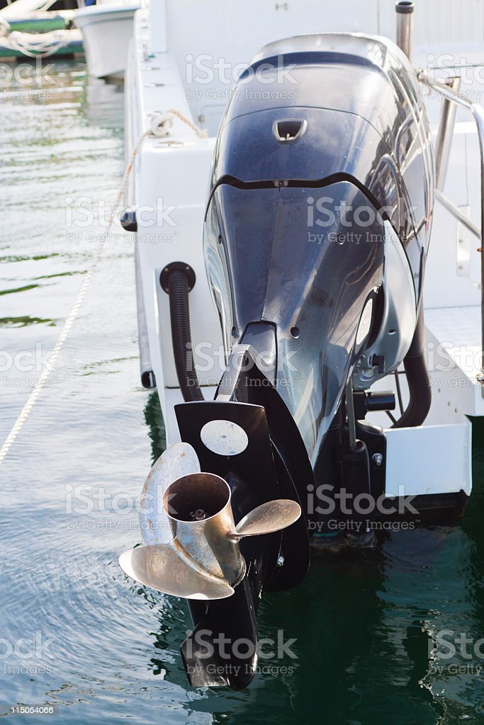Boat engine with propeller attached on motorboat in marina stock photo