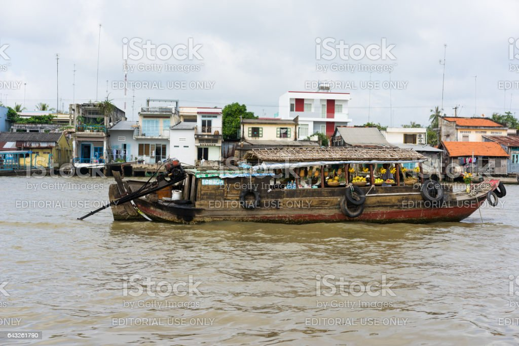 Tien Giang, Vietnam - Nov 28, 2014: Boat filled with fruits, vegetables and other products on sale on Cai Be floating market on Tien river, border between Tien Giang, Vinh Long and Ben Tre Provinces stock photo