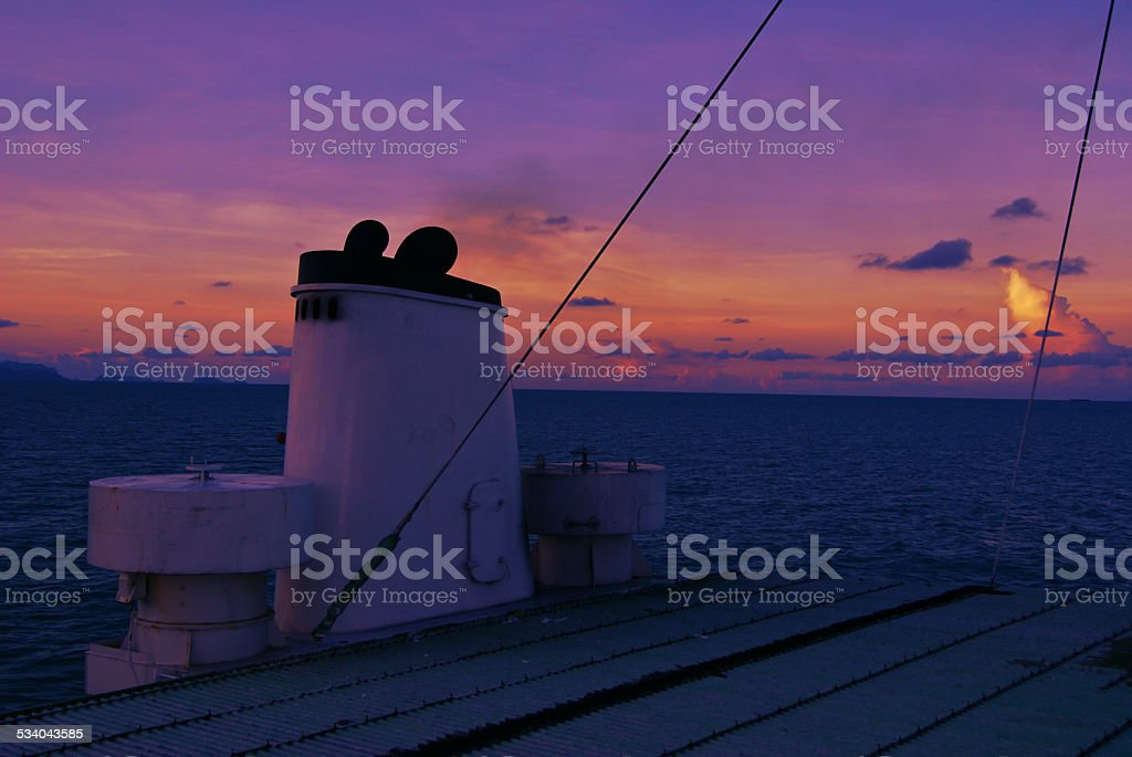 boat gliding in sea at sunset stock photo