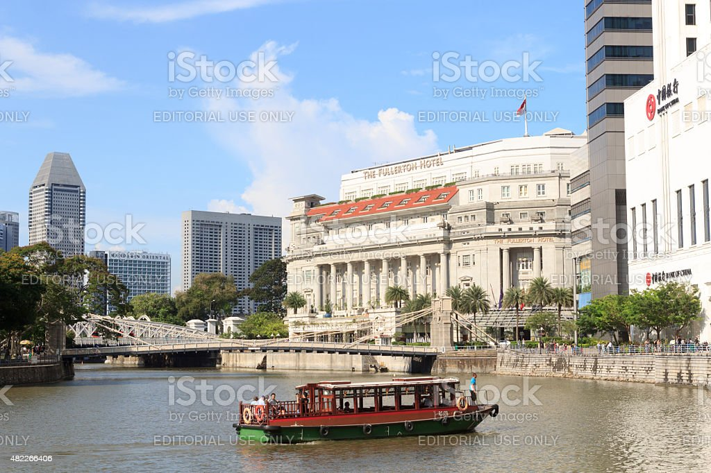 Boat in front of Cavenagh bridge and Fullerton Hotel, Singapore stock photo
