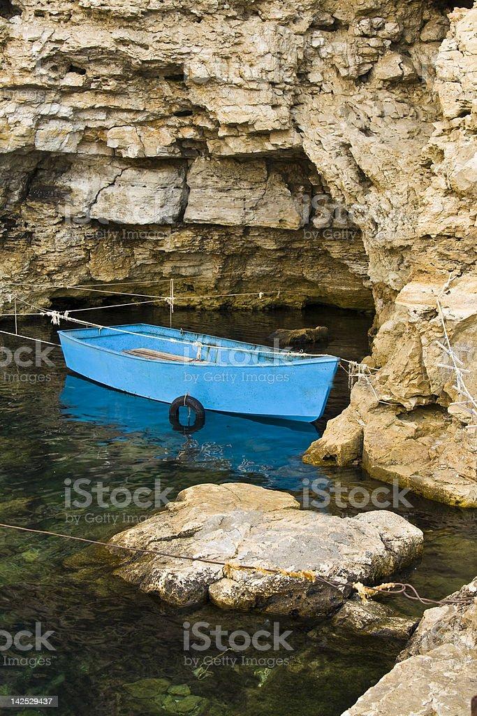 Boat in rocks stock photo
