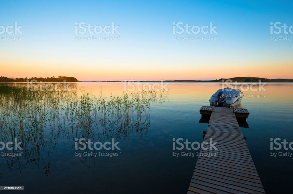 Boat in Sunset on Calm Lake in Finland stock photo