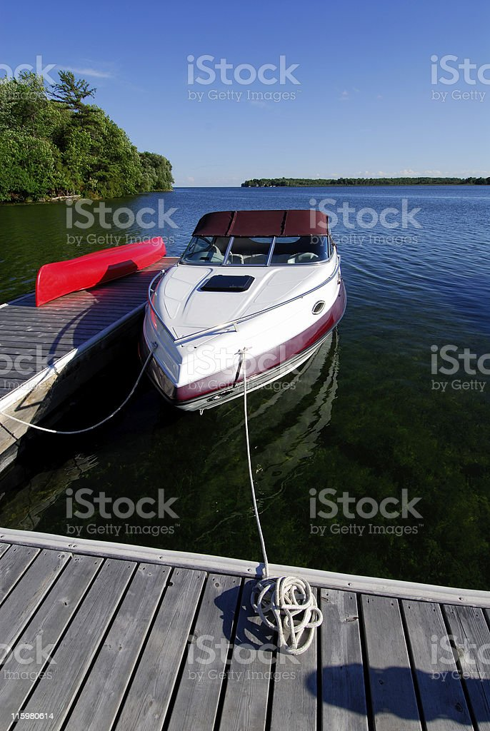 Boat in the water tied to a wooden cottage dock stock photo