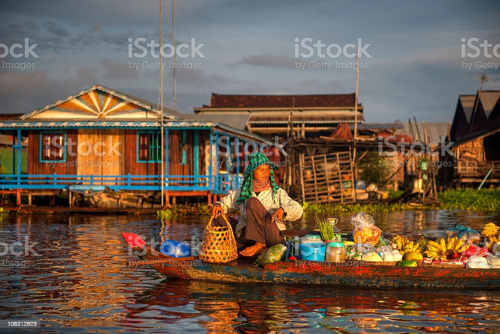 Boat in water in front of colorful Cambodian village  stock photo