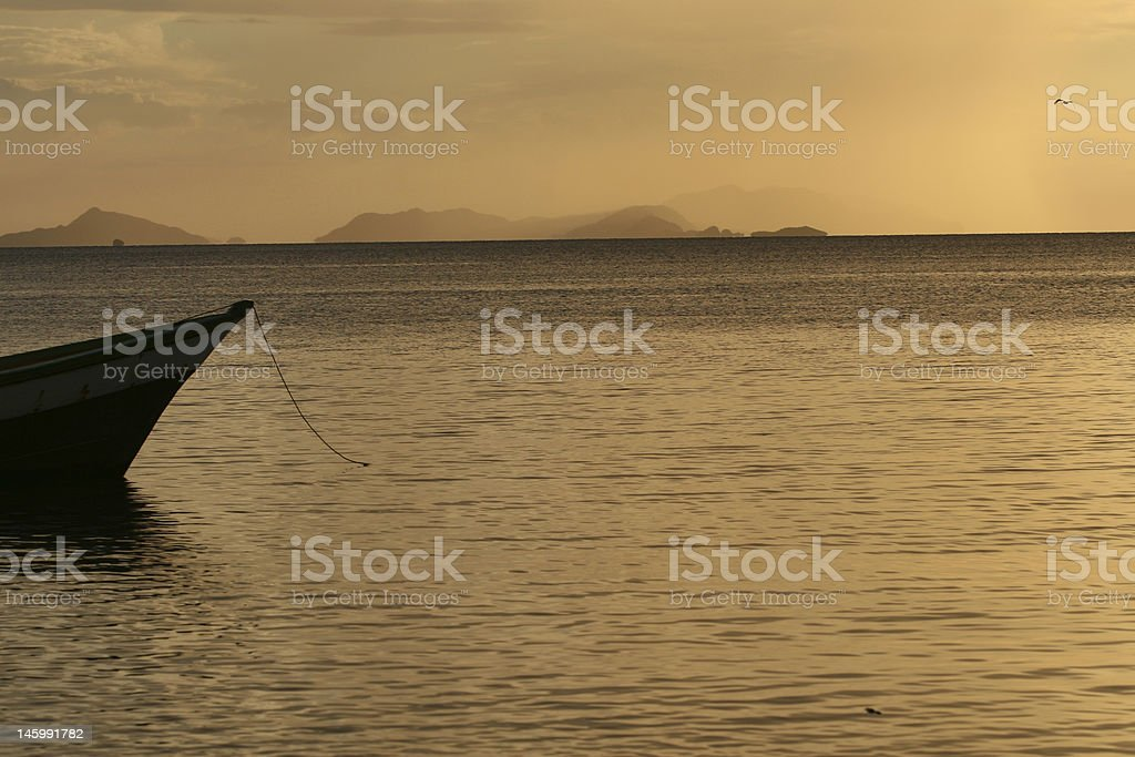 Boat is anchored at harbour under sunset royalty-free stock photo