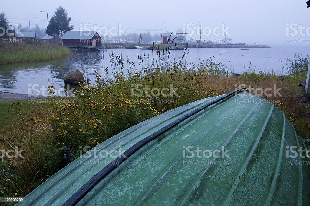 Boat laying overturned next to beach stock photo