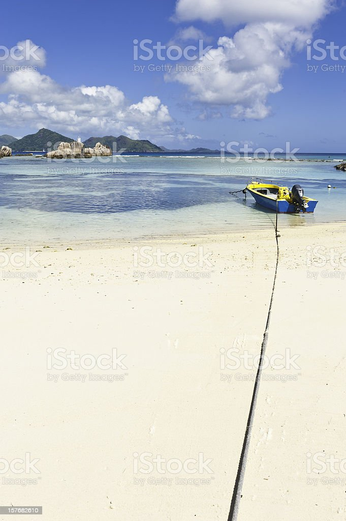 Boat moored in turquoise lagoon beside idyllic tropical island beach royalty-free stock photo