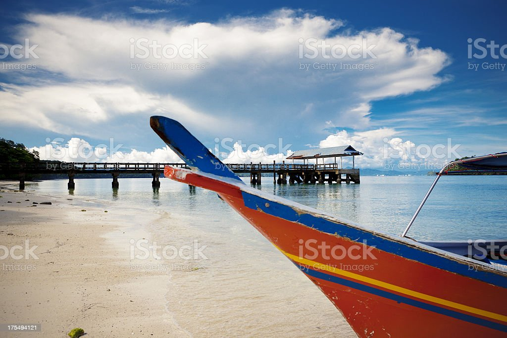 Boat on a beach with dock in the distance royalty-free stock photo