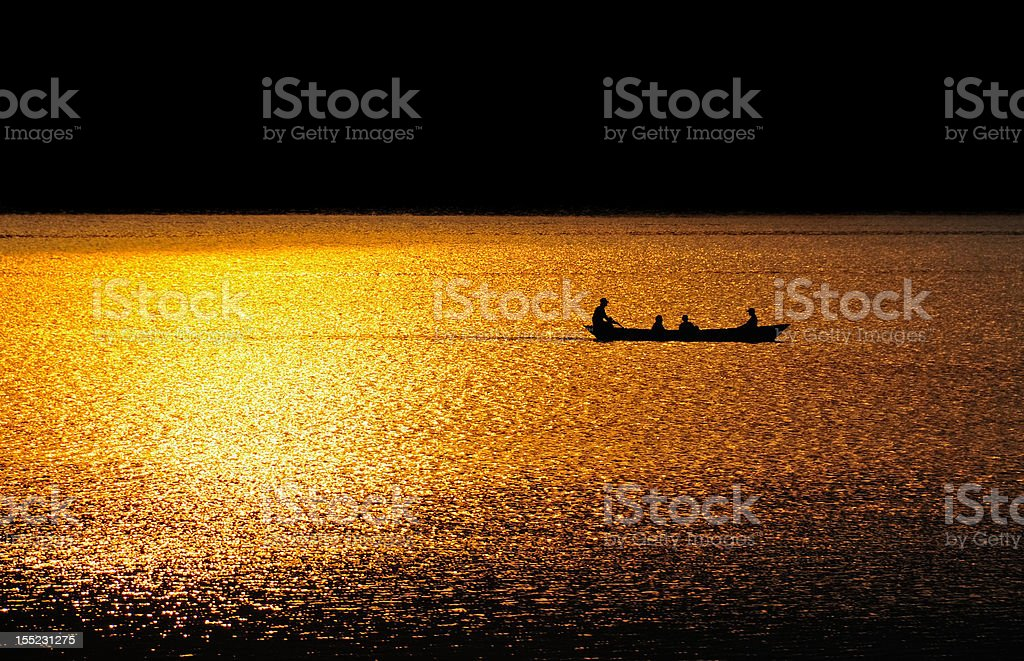 Boat on a lake at sunset stock photo