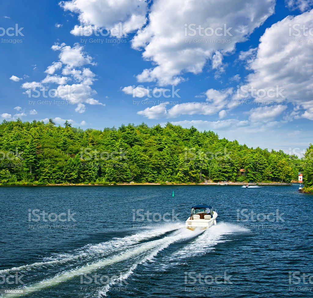 A boat on a lake surrounded by trees stock photo