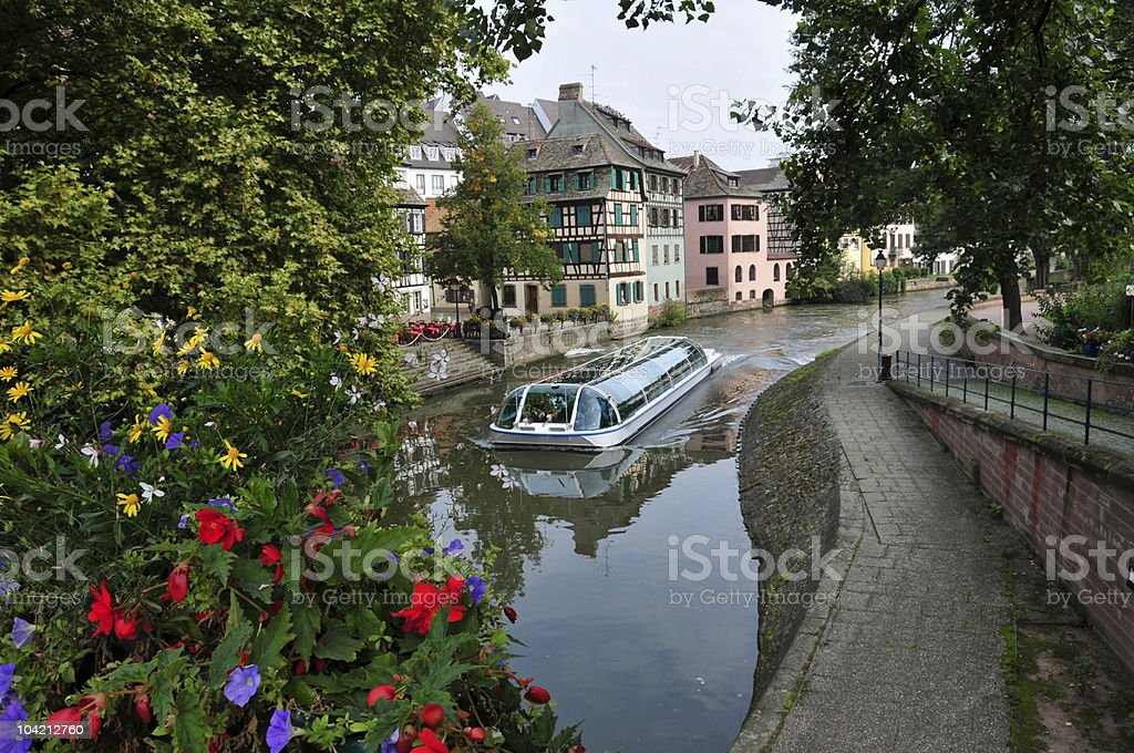 Boat on Canal, Flowers Foreground, Houses in Background stock photo