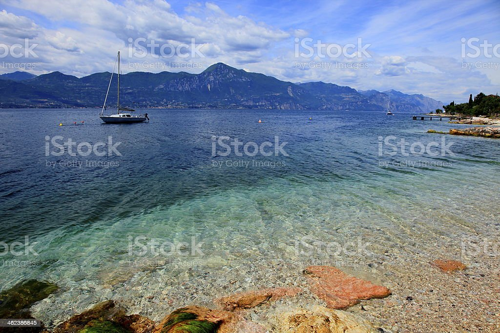 Boat on idyllic and turquoise Lake Garda, Malcesine - Italy stock photo