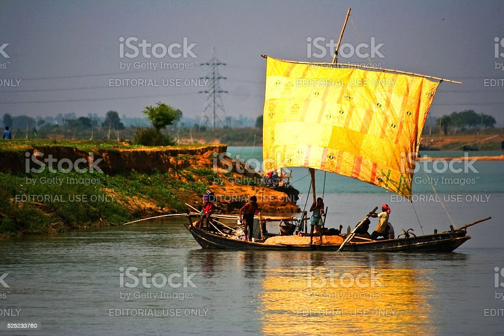 Boat on river collecting sand fron river bed stock photo