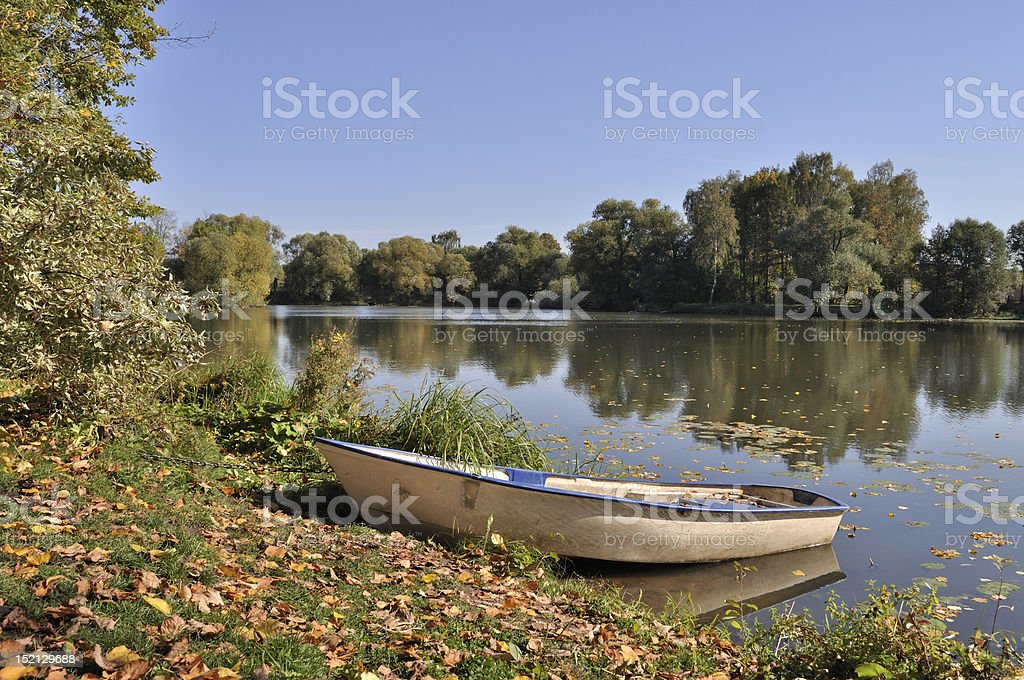 Boat on the lake bank in autumn royalty-free stock photo