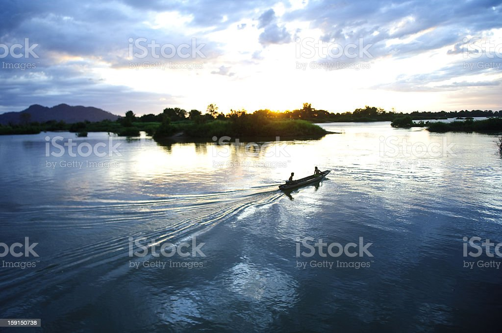 boat on the mekong river by sunset stock photo