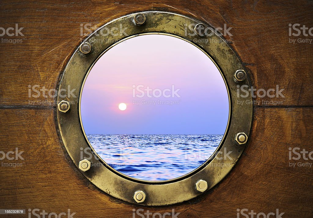 A boat porthole with the view of the sunset stock photo