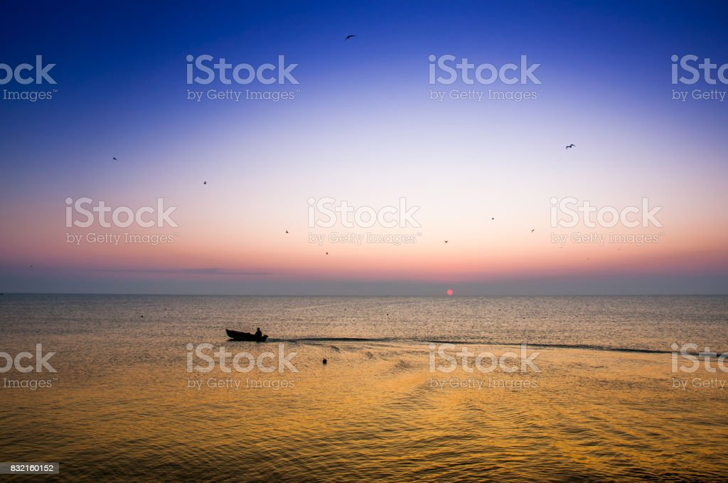 Boat ride during sunrise on the sea. stock photo